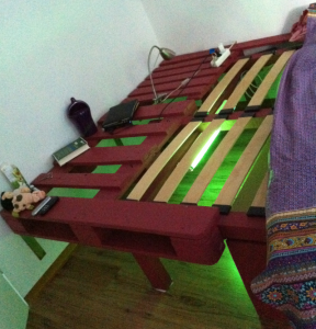 Double bed made of pallets and timber beams, neon illumination